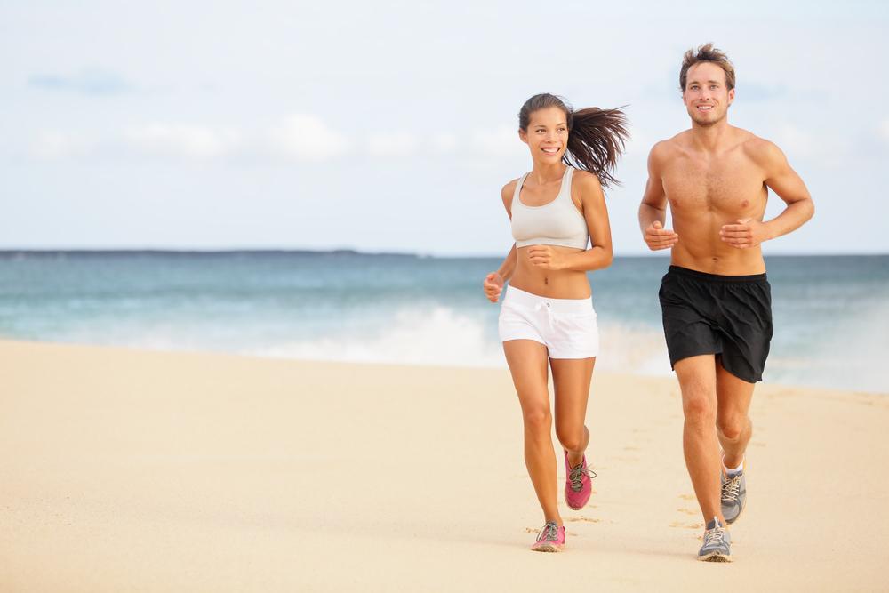 Couple running at beach wearing athleisure shorts